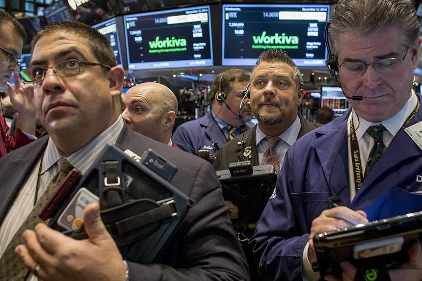 Traders work on the floor of the New York Stock Exchange Dec 12, 2014. The Dow plummeted more than 300 points Friday as US stocks took cues from a rout in European equities following another big drop in oil prices.-- PHOTO: REUTERS