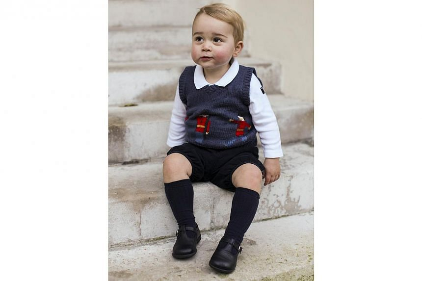 Britain's Prince George of Cambridge sitting in a courtyard at Kensington Palace in London. -- PHOTO: AFP