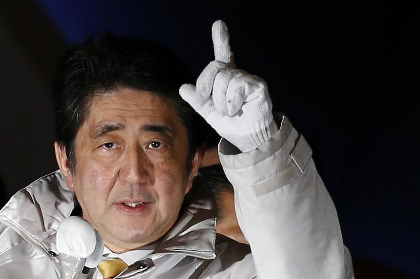 Japanese Prime Minister Shinzo Abe comfortably won re-election on Sunday, Dec 14, 2014, with his ruling coalition securing an unassailable majority in the lower house, media exit polls showed. -- PHOTO: REUTERS