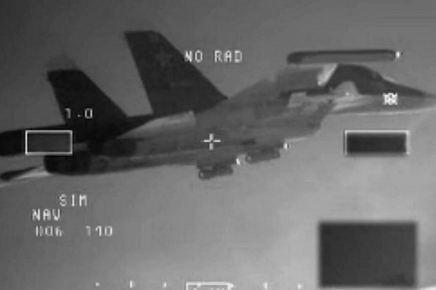 """A handout photo released on Dec 11, 2014 by the Dutch Defence ministry shows one of the two Russian SU-34 """"Fullback"""" bombers being intercepted by Dutch F-16's over the Baltic Sea on Dec 8.Russia's defence ministry on Sunday denied a report by S"""