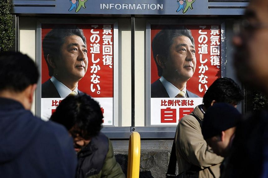 Posters of Japan's Prime Minister Shinzo Abe, who is also the leader of the ruling Liberal Democratic Party (LDP), are seen as members of media stand in front of the LDP headquarters in Tokyo on Dec 14, 2014. -- PHOTO: REUTERS