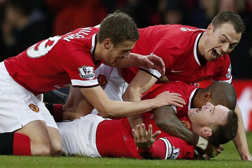Manchester United's Wayne Rooney (on ground) celebrates with Michael Carrick (left), Jonny Evans (right) and Ashley Young (partially obscured), after scoring the opening goal during their English Premier League football match against Liverpool at Old