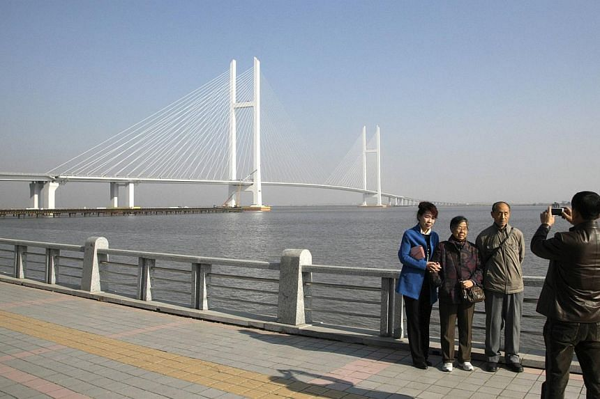 People pose for pictures with the new Friendship Bridge over the Yalu River, connecting China's Dandong and North Korea's Sinuiju, on Nov 9, 2014. North Korea on Sunday, Dec 14, put on display an American who had apparently entered the country i