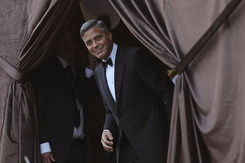 US actor George Clooney smiles as he arrives by taxi boat to the venue of a gala dinner ahead of his official wedding ceremony in Venice in this Sept 27, 2014, file photo. -- PHOTO: REUTERS