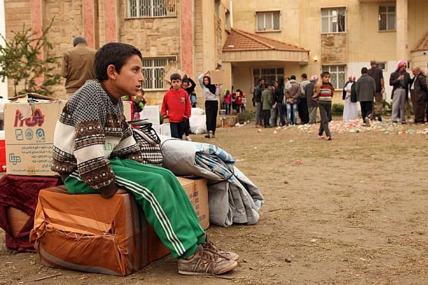 A displaced boy who fled Islamic State violence in Mosul, sits in a school in Dohuk province, Dec 1, 2014. Britain will send hundreds of troops to train Iraqi and Kurdish forces in Iraq, Defence Secretary Michael Fallon told The Daily Telegraph