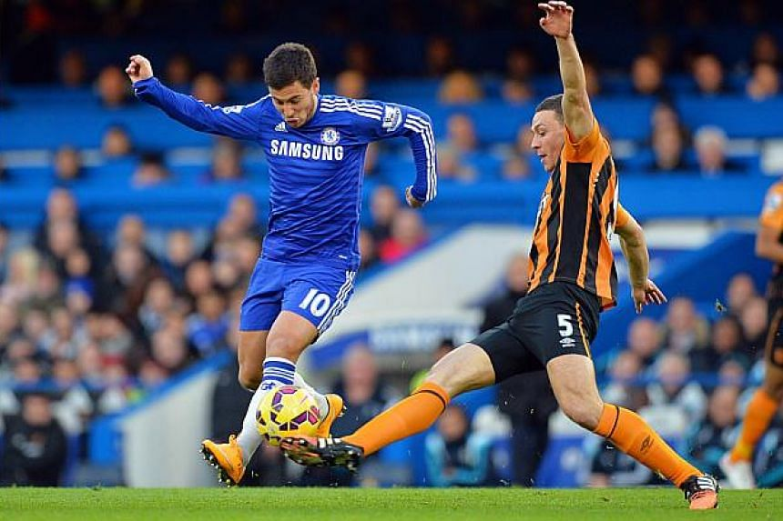 Chelsea's Belgian midfielder Eden Hazard (left) vies with Hull City's English defender James Chester (right) during the English Premier League football match between Chelsea and Hull City at Stamford Bridge in London on Dec 13, 2014. Leaders Chelsea