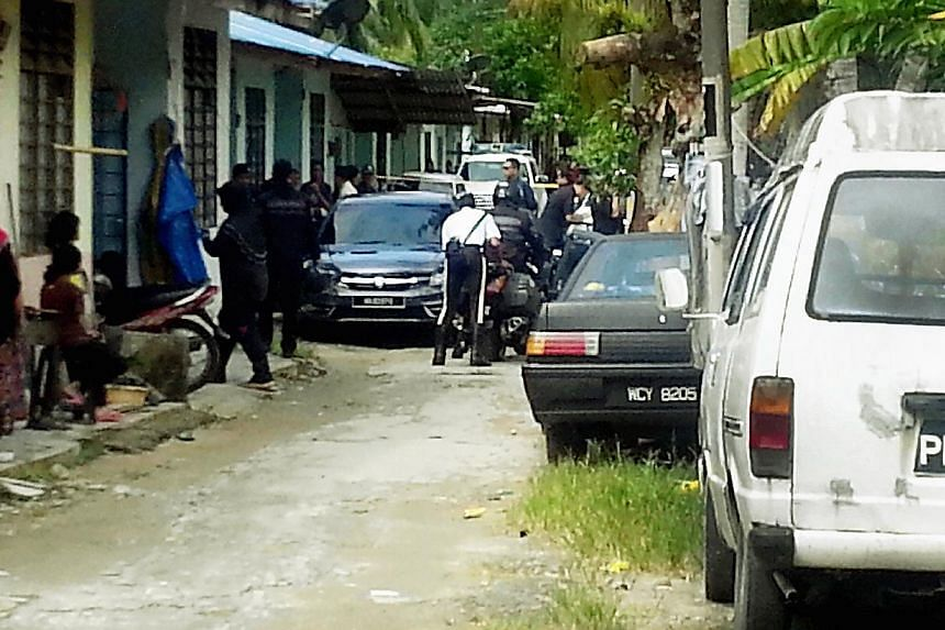 Police at a house in Kampung Pisang, Cherok Tok Kun, where some of the grisly murders of Myanmar nationals took place. Police are now hunting for a fourth suspect believed to be behind the gruesome murders in Penang this year. -- PHOTO: THE MALAY MAI