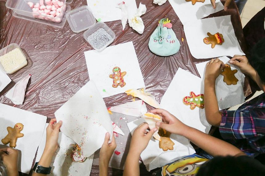 Marsiling residents decorating their gingerbread men at a family carnival on Dec 14, 2014.-- ST PHOTO:ONG WEE JIN
