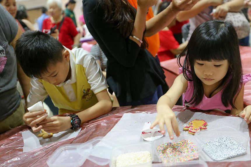Hazel Liew Xi Xuan (right), 5, decorating her gingerbread manat theMarsiling Family Fiesta on Dec 14, 2014.-- ST PHOTO:ONG WEE JIN