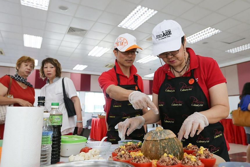 Jenny Toh Chor Kheng (right), 54, putting the finishing touches to his dish in the cooking competition at theMarsiling Family Fiesta on Dec 14, 2014.-- ST PHOTO:ONG WEE JIN