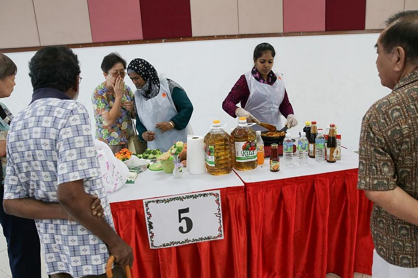 Residents of Marsiling watching one of nine teams in the cooking competition at theMarsiling Family Fiesta on Dec 14, 2014.-- ST PHOTO:ONG WEE JIN