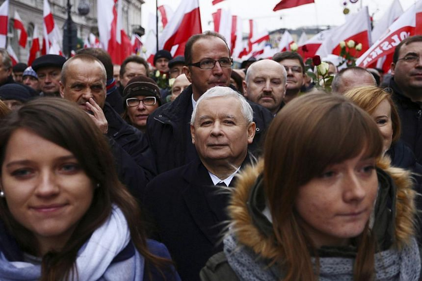 Jaroslaw Kaczynski (centre rear), leader of the Polish Law and Justice (PiS) party, takes part in a demonstration march in Warsaw Dec 13, 2014.Several thousand Polish opposition supporters marched in the capital Warsaw on Saturday to denounce a