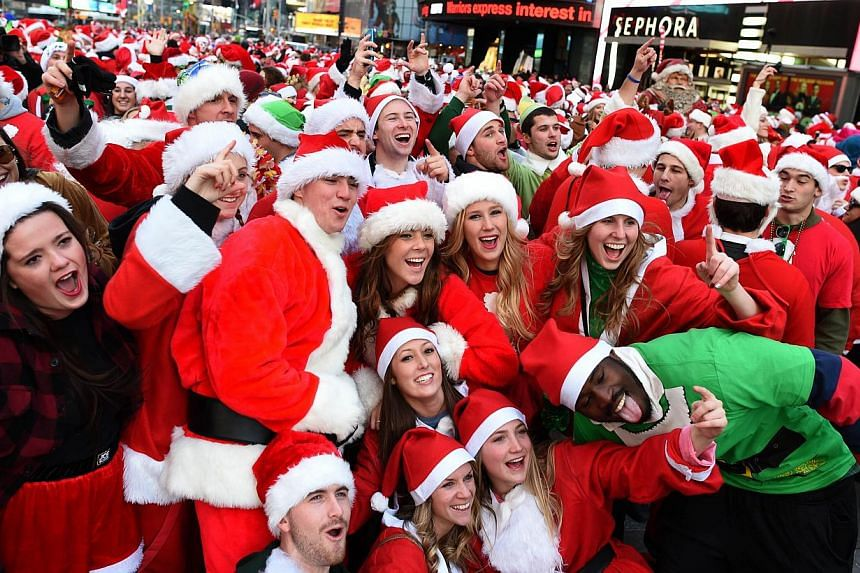 People dressed as Santa Claus and Mrs Claus pose in Times Square as they gather for the annual Santacon festivities on Dec 13, 2014 in New York. -- PHOTO: AFP