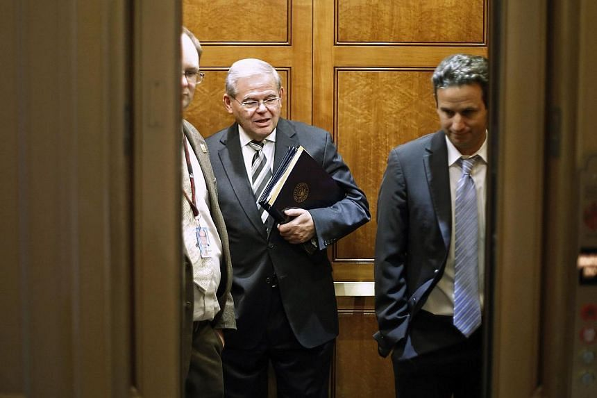 U.S. Senator Robert Menendez (center) and Senator Brian Schatz (right) board an elevator as they take a break from a long series of votes, many on procedural matters or to confirm members of the Obama administration, at the U.S. Capitol in Washington