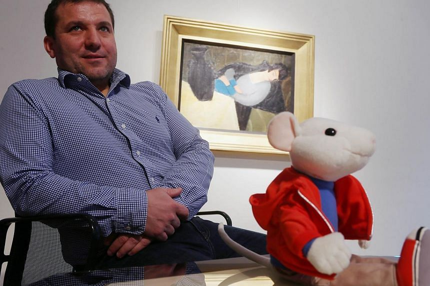 "Hungarian art historian Gergely Barki poses next to a plush figure of the Stuart Little character in front of the painting  ""Sleeping Lady with Black Vase"" in Budapest on Nov27, 2014.  A long-lost avant-garde painting went under the au"