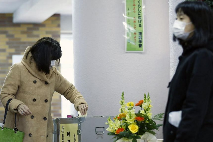 A woman casts her ballot to vote for members of the supreme court as part of Japan's general election in Tokyo on Dec 14, 2014. -- PHOTO: REUTERS