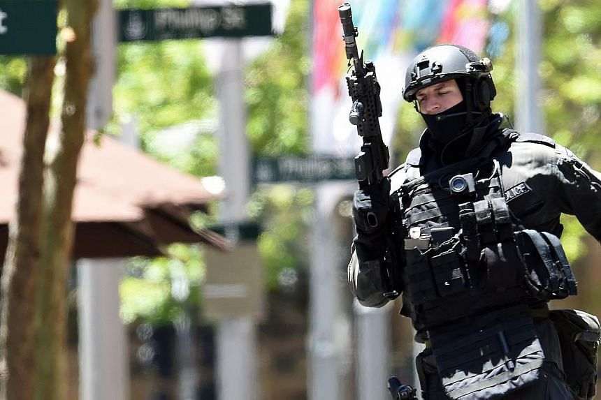 An armed policeman is seen outside a cafe in the central business district of Sydney on Dec 15, 2014. -- PHOTO: AFP