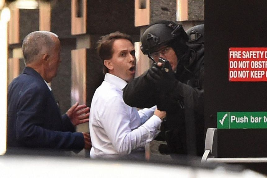 Two hostages (left) run for cover behind a policeman (right) during a hostage siege in the central business district of Sydney on Dec 15, 2014. -- PHOTO: AFP
