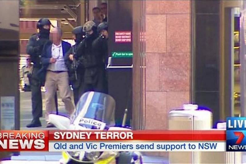 Hostages were shown running out of a Sydney cafe at the centre of a siege on Monday, according to Channel 7 live news footage. -- PHOTO:SCREENGRAB FROM CHANNEL 7