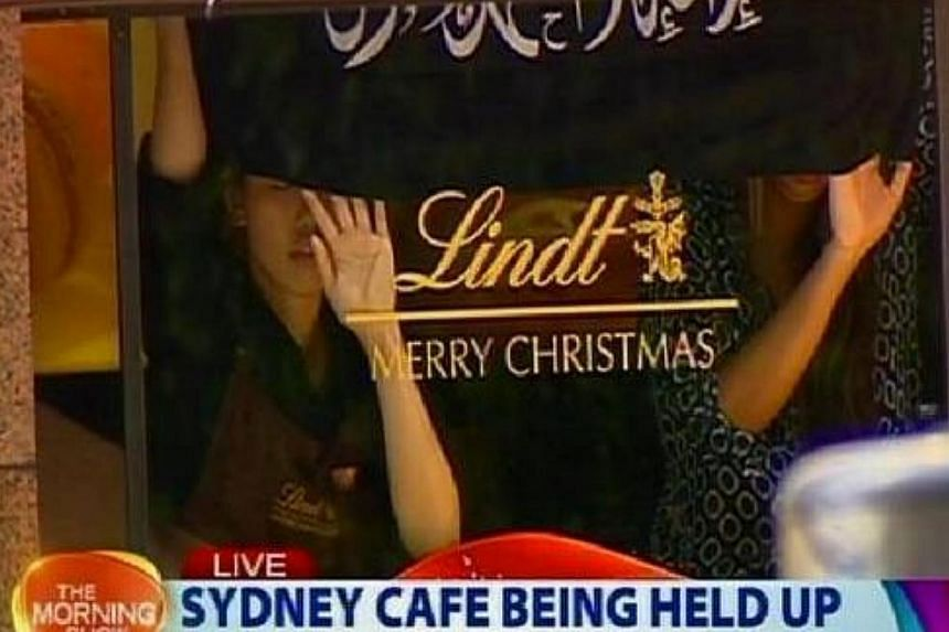 Hostages seen holding up a black flag with white Arabic writing inside Lindt Chocolat Cafe in Sydney. -- PHOTO: THE MORNING SHOW