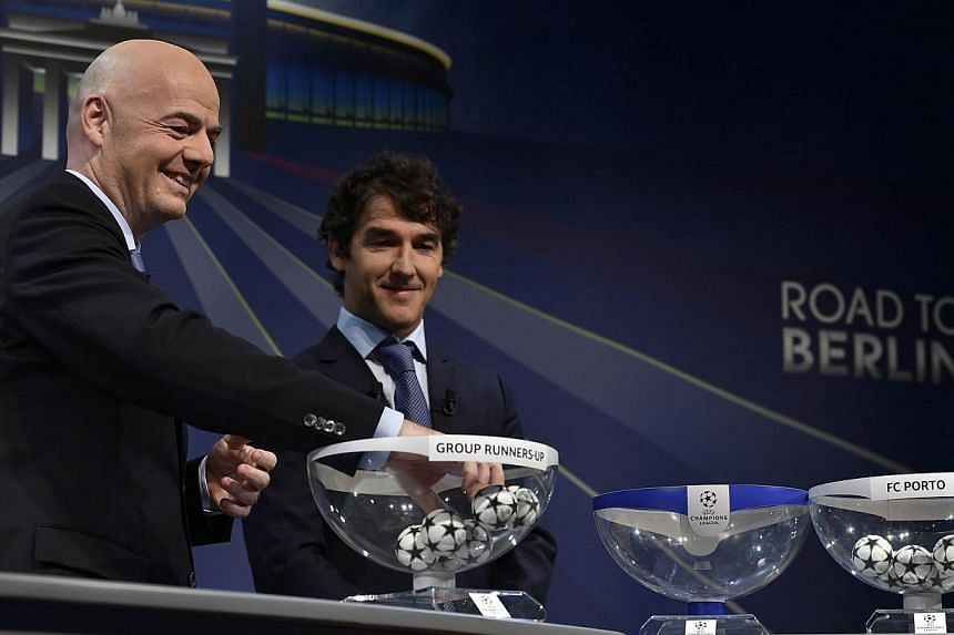 Uefa General Secretary Gianni Infantino picks a ball next to the ambassador for the Uefa Champions League final in Berlin Karl-Heinz Riedle (right) during the draw for the Uefa Champions League round of 16 on Dec 15, 2014 at the Uefa headquarters in