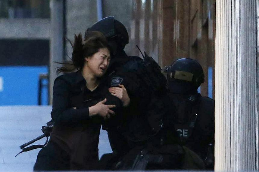 A hostage runs towards a police officer outside Lindt cafe, where other hostages are being held, in Martin Place in central Sydney on Dec 15, 2014. -- PHOTO: REUTERS