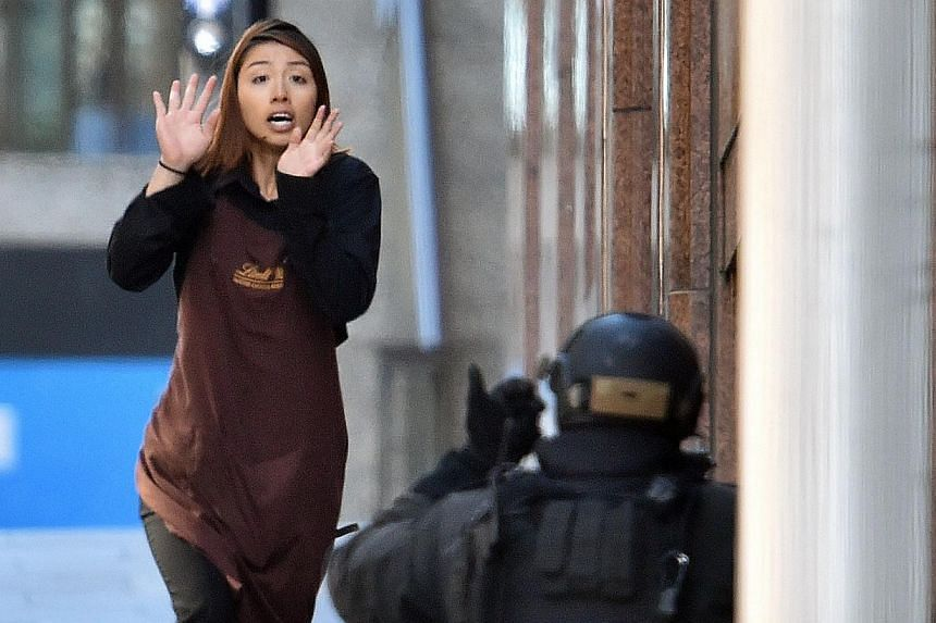 One of the hostages runs towards police from a cafe in the central business district of Sydney on Dec 15, 2014. -- PHOTO: AFP