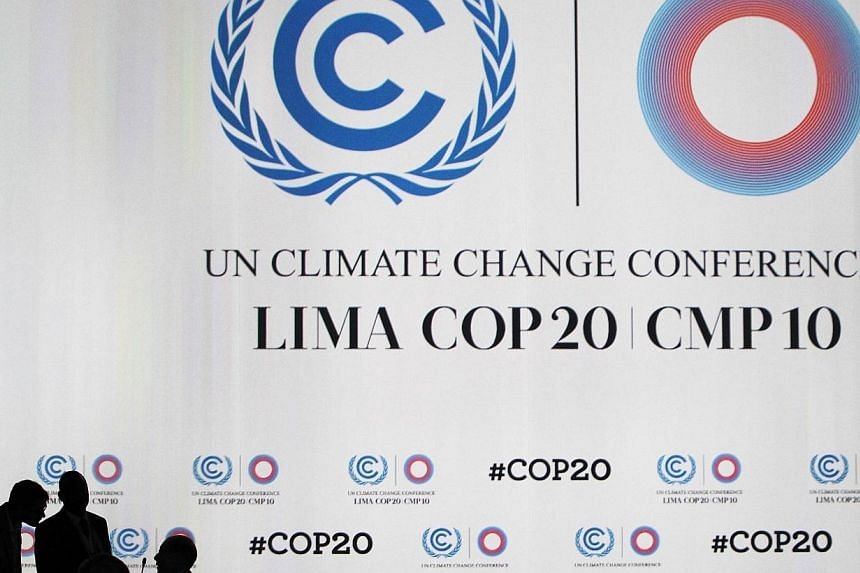 Delegates talk during a break at a plenary session of the UN Climate Change Conference COP 20 in Lima on Dec 12, 2014. -- PHOTO: REUTERS