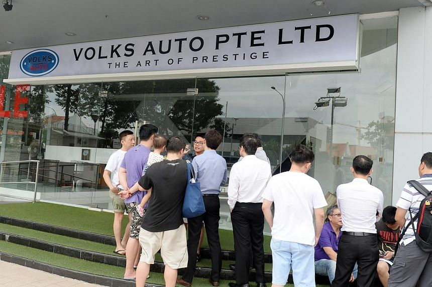 More than 20 people gathered outside a car dealership at MacPherson Road on Monday, after the dealership failed to deliver the cars they had bought. They wanted to look for the owner, whom they say have been uncontactable for a few days. -- ST PHOTO: