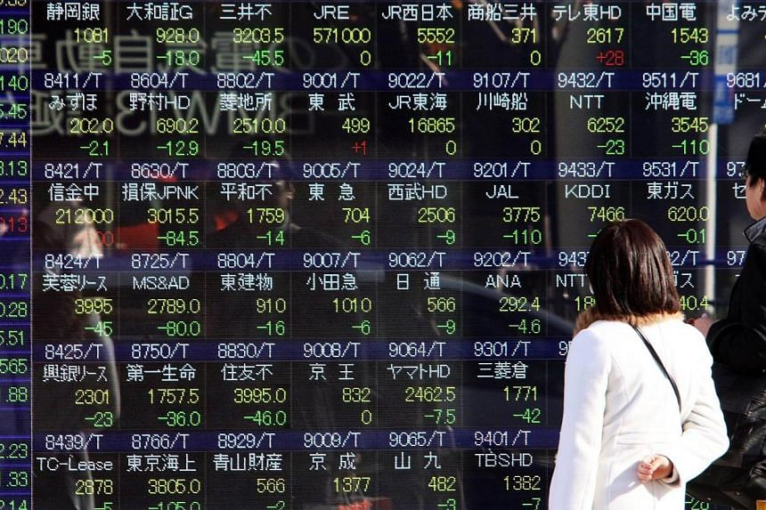 Pedestrians gaze at a share prices board in Tokyo on Dec 15, 2014.Japan's Nikkei share average fell 1.6 per cent, drawing little momentum from Japanese Prime Minister Shinzo Abe's big election victory on Sunday, which was a boost for his reflat