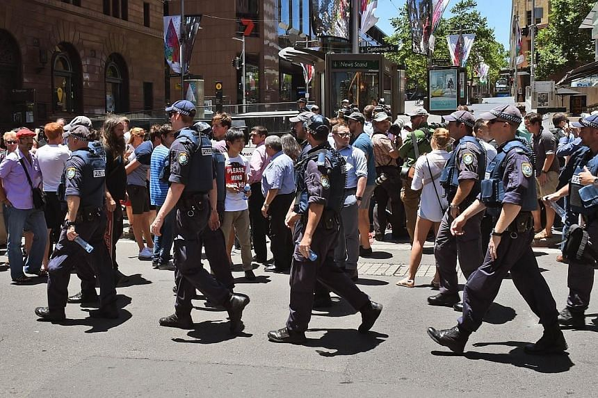 Police walk through Martin Place as spectators look on during a hostage siege in the central business district of Sydney on Dec 15, 2014.Singapore's Ministry of Foreign Affairs (MFA) has reminded Singaporeans in Sydney to take extra precaution