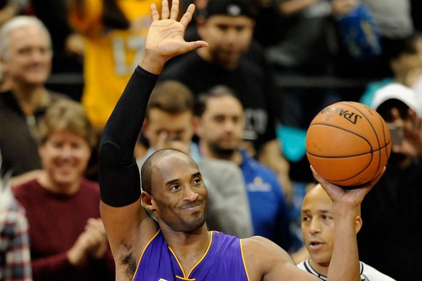 Kobe Bryant #24 of the Los Angeles Lakers waves to the crowd on Dec 14, 2014 at Target Center in Minneapolis, Minnesota. -- PHOTO: AFP
