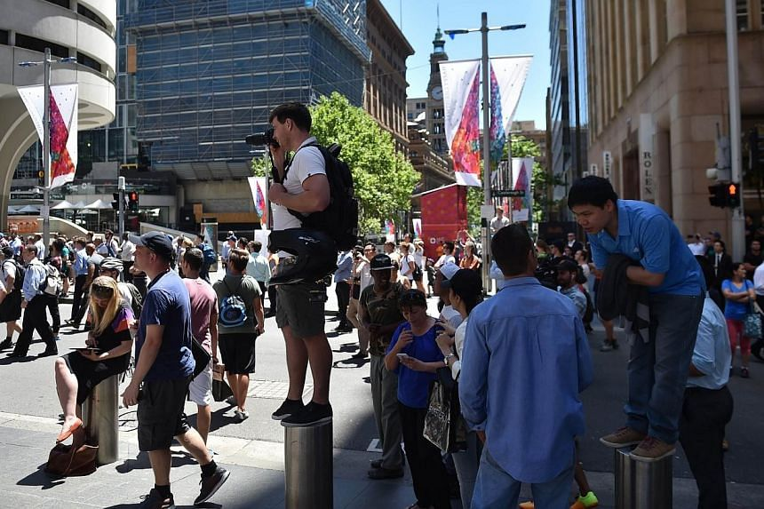 Journalists and onlookers gather in Martin Place in the central business district of Sydney on Dec 15, 2014.Australian police said on Monday they are monitoring alleged demands made on social media by hostages being held in a siege at a Sydney