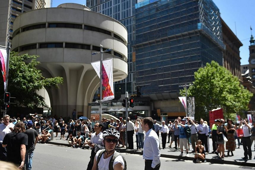 Onlookers gather in Martin Place in the central business district of Sydney on Dec 15, 2014. New South Wales police commissioner Andrew Scipione praised the Sydney public for its calm and cooperative reaction to the lockdown of part of the city'