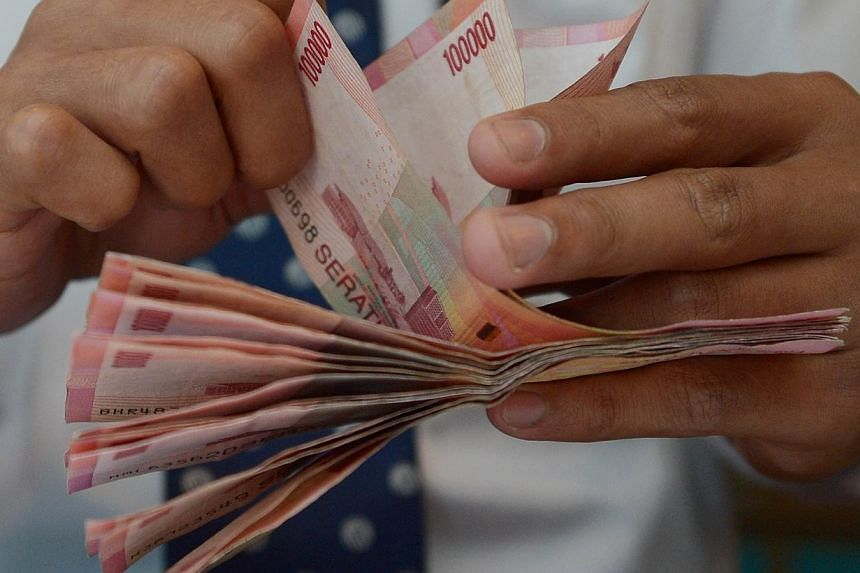 A teller counts Indonesian bank notes at a bank in Jakarta on Dec 15, 2014.Both the Malaysian ringgit and Indonesian rupiah have reached record lows at about the same time. -- PHOTO: AFP