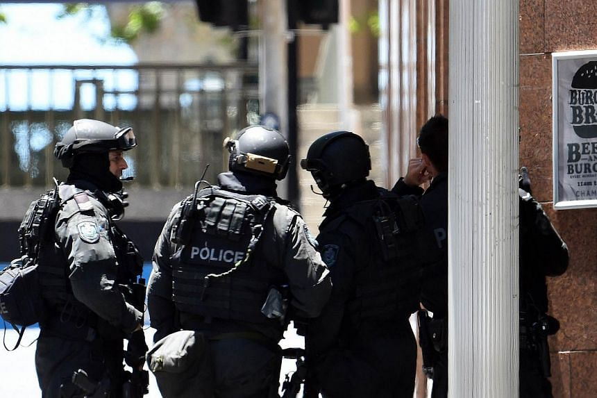 Armed police stay at the main entrance of Lindt Chocolat Cafe in the central business district of Sydney on Dec 15, 2014. -- PHOTO: AFP