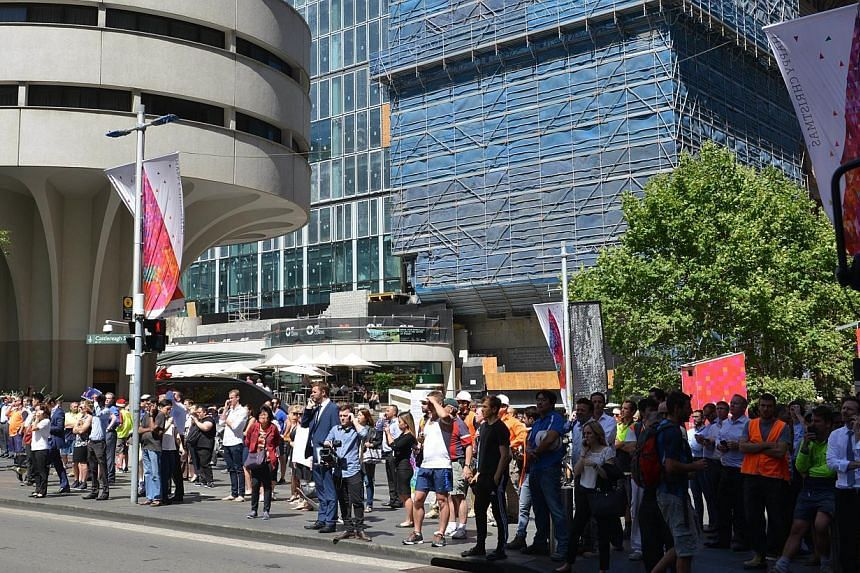 People look on as events unfold on a street where a cafe is being used to hold hostages in the central business district of Sydney on Dec 15, 2014. -- PHOTO: AFP