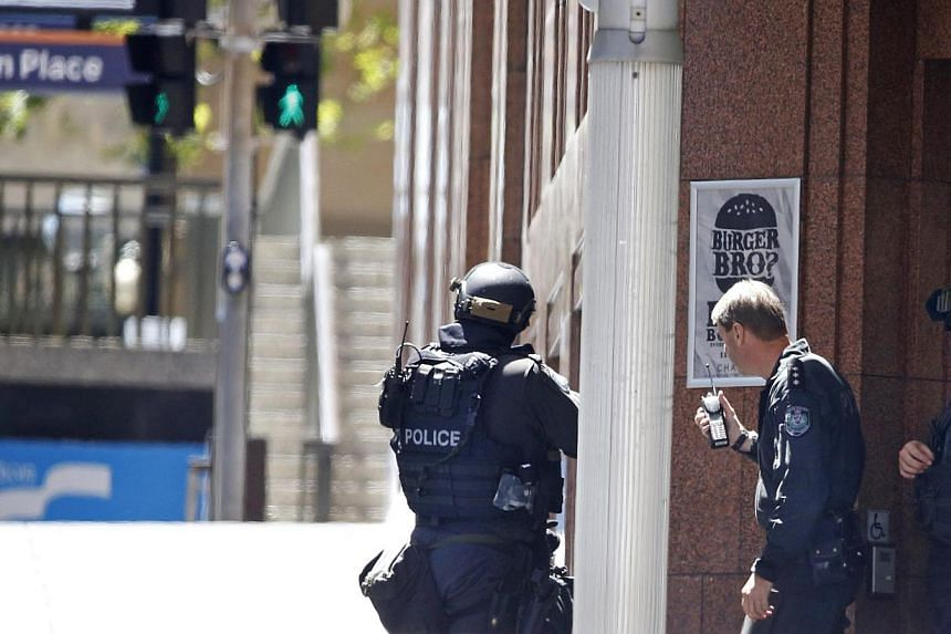 New South Wales state police officers are seen at a corner near Lindt cafe in Martin Place, where hostages are being held, in central Sydney on Dec 15, 2014. -- PHOTO: REUTERS