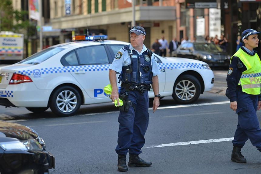 Police close a street where a cafe is being used to hold hostages in the central business district of Sydney on Dec 15, 2014. -- PHOTO: AFP
