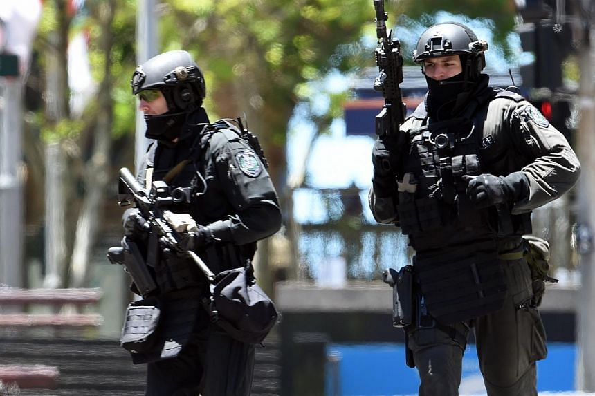 Armed police are seen outside a cafe in the central business district of Sydney on Dec 15, 2014.-- PHOTO: AFP