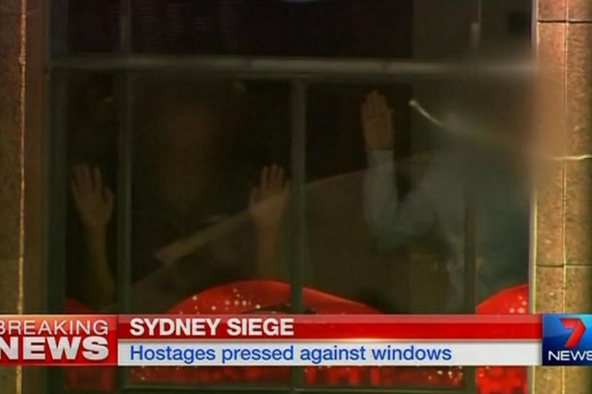 Hands are pressed up against the window of the Lindt cafe in Sydney, where hostages are being held, in this still image taken from video from Australia's 7 Network on Dec 15, 2014. -- PHOTO: REUTERS