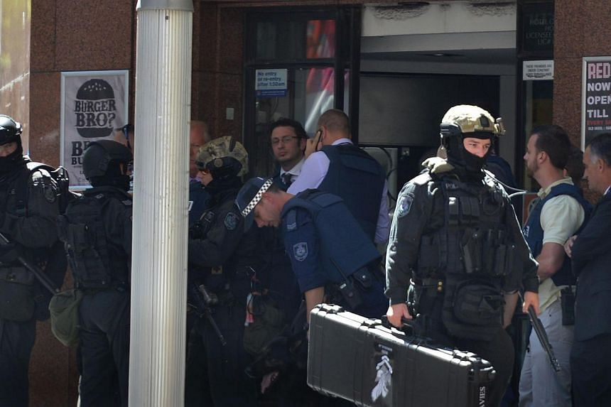 Armed police are seen outside a cafe in the central business district of Sydney where hostages were being held inside on Dec 15, 2014. -- PHOTO: AFP