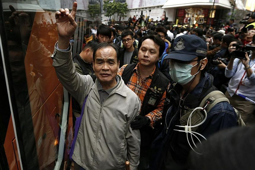 A pro-democracy protester chants slogans as he is taken away by the police during a clearance at the last protest site blocking a main road at Causeway Bay shopping district in Hong Kong on Dec 15, 2014. -- PHOTO: REUTERS