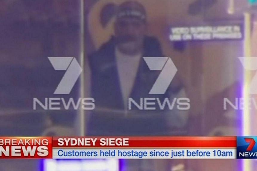 A man is seen standing behind the window of the Lindt cafe, where hostages are being held, in this still image taken from video from Australia's Seven Network on Dec 15, 2014. -- PHOTO: REUTERS