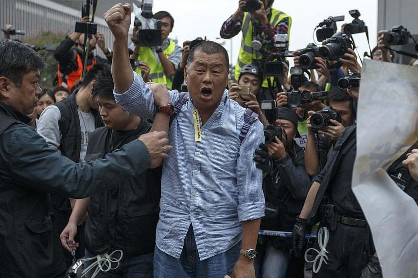 Tycoon and Apple Daily Newspaper owner Jimmy Lai shouts slogan before he is taken away by police officer at an area previously blocked by pro-democracy supporters, outside the government headquarters in Hong Kong on Dec 11, 2014. -- PHOTO: REUTERS
