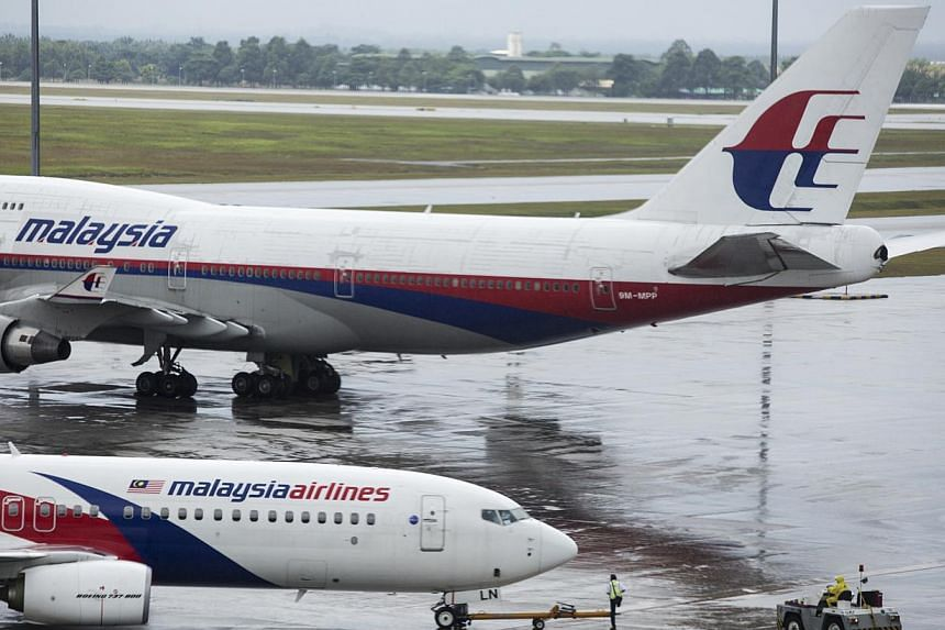 Malaysia Airlines suspended its shares from the country's stock exchange Monday under a government rescue plan for the flag carrier which is fighting for survival after losing two planes this year. -- PHOTO: BLOOMBERG