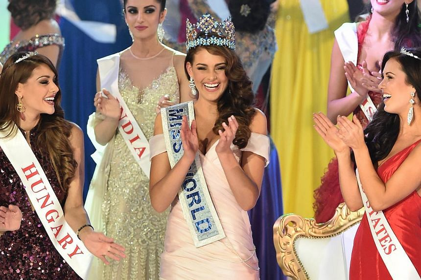 Miss South Africa and the 2014 Miss World, Rolene Strauss (centre), dances with first runner up Miss Hungary Edina Kulcsar (left) and second runner up Miss United States Elizabeth Safrit (right) during the grand final of the Miss World 2014 pageant a