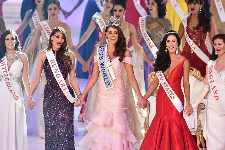 Miss South Africa and the 2014 Miss World, Rolene Strauss (centre), holds hands with first runner up Miss Hungary Edina Kulcsar (left) and second runner up Miss United States Elizabeth Safrit (right) after being crowned during the grand final of the