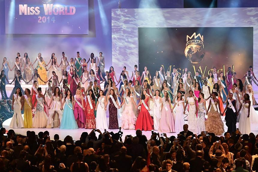 All contestants hold hands after Miss South Africa and the 2014 Miss World, Rolene Strauss (centre), was crowned during the grand final of the Miss World 2014 pageant at the Excel London ICC Auditorium in London on Dec 14, 2014. -- PHOTO: AFP