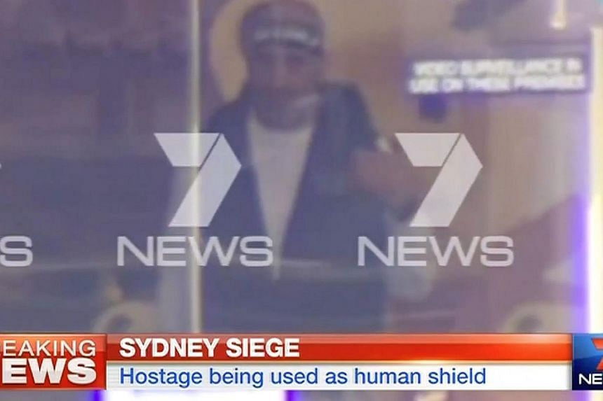 This screengrab taken from Australian Channel Seven shows the suspected gunman inside a cafe in the central business district of Sydney on Dec 15, 2014. -- PHOTO: AFP